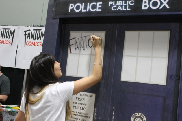 Esther Kim of Fantom Comics draws her shop's logo on the TARDIS