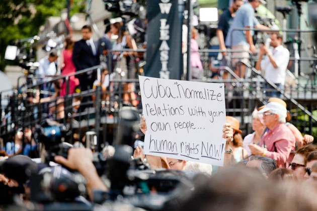 A protester holds a sign among a throng of news media.