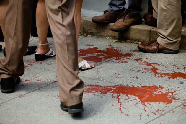 Fake blood on sidewalk outside the gates of the embassy
