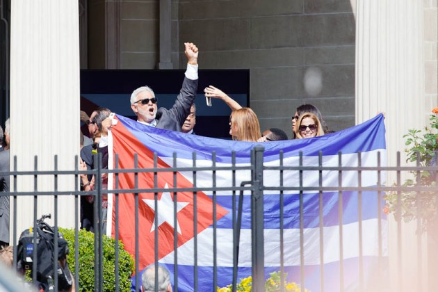 Cuban officials hold up a flag