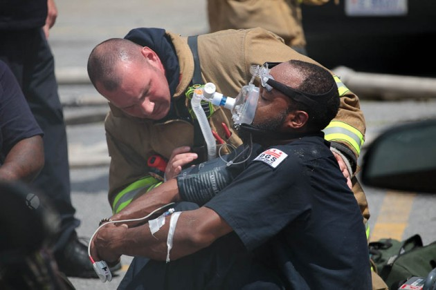 Firefighters give oxygen to man rescued from fire.