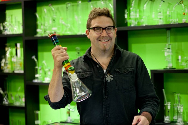 Shop co-owner Adam Eidinger holding an artisan-made bong