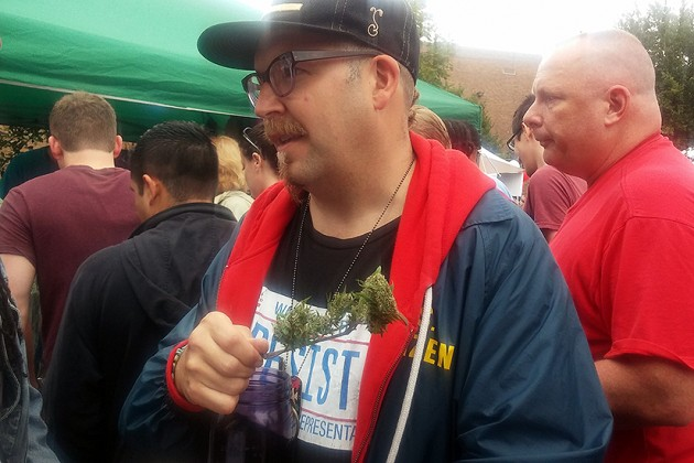 Capital Hemp owner and marijuana activist leader Adam Eidinger holding homegrown pot