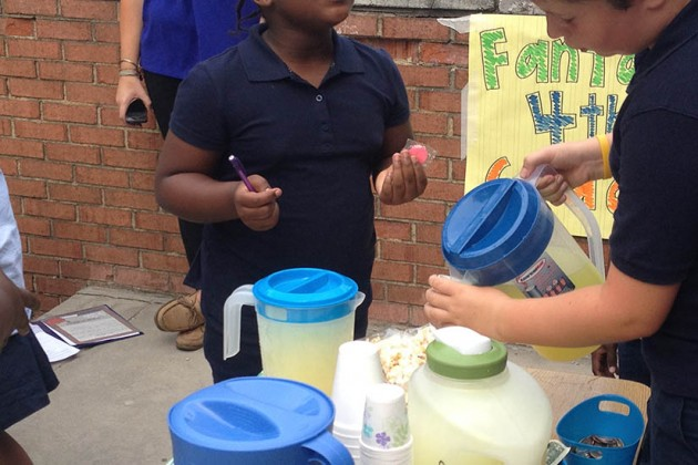 A fourth grader serves lemonade to a customer during Garrison Elementary's  Lemonade Wars.