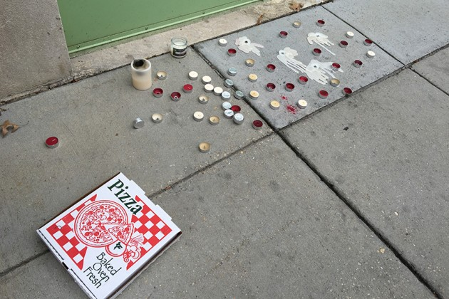 A pizza box and melted candles in front of the eatery on Sunday morning