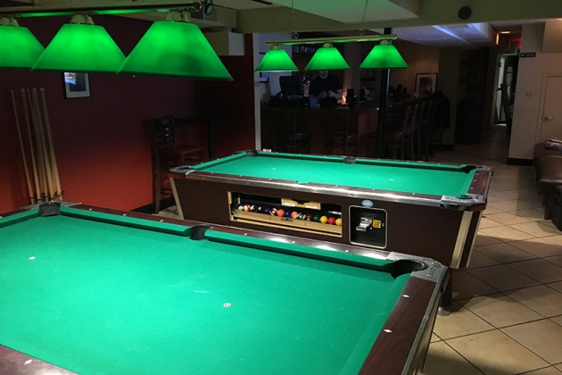 The bar has two pool tables and multiple TVs