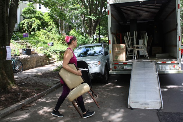 Collective member loading the last pieces of furniture into a moving truck